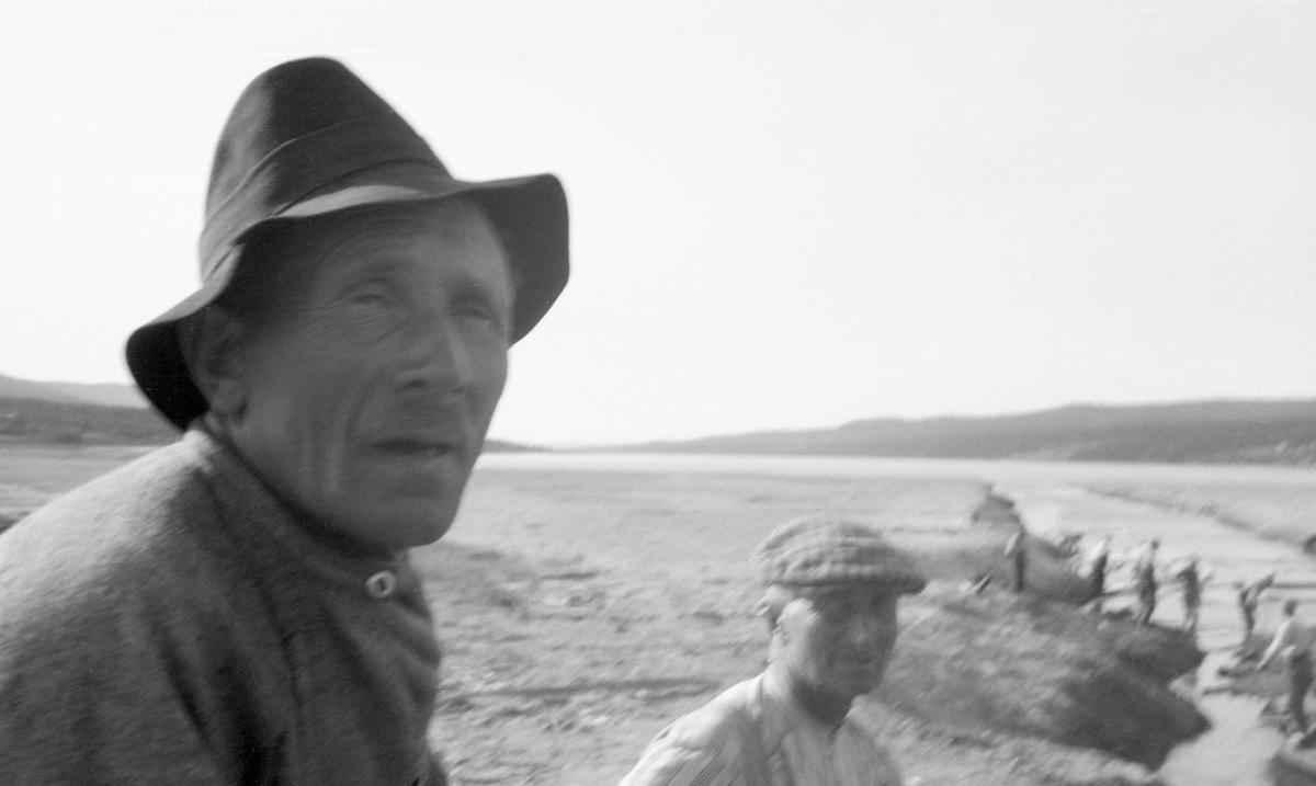 Kanalen som danner utløp var Vesle-Osen lengst sør i Osensjøen mot sjølve sjøen i 1942.  Bildet viser ansiktene på to av fløterne.  Ansiktstrekkene trer dessverre ikke fullkomment fram, dels på grunn av motlys, dels på grunn av at opptaket wer noe uskarpt. Begge fløterne har busseruller på seg, den ene har hatt, den andre sixpencelue på hodet.  I bakgrunnen skimtes en rekke arbeidskamerater langs kanalens bratte, sandete bredder. Kanalen mellom Osensjøen og Vesle-Osen var for øvrig et vanskelig sted å fløte tømmer, blant annet fordi skiftninger i strømningene i sjøen kunne drive tømmeret sørover igjen.