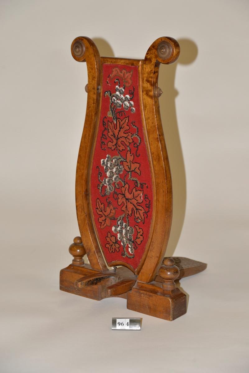 Stövelknekt bestående av en lyrformad träställning med en mittplatta av röd textil prydd av broderi.