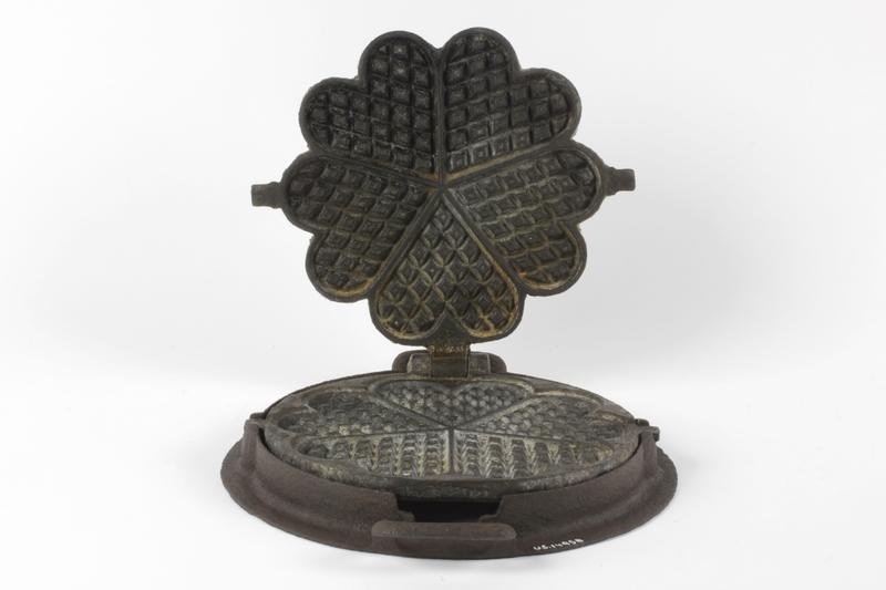 Dette vaffeljernet fra Ullensakers gjenstandssamling er produsert av O. Mustad & Søn som holdt til på Gjøvik. Denne typen vaffeljern er laget for bruk på vedovn. Jernet ble da plassert på en ring, som passet i varmehullet på vedovnen.