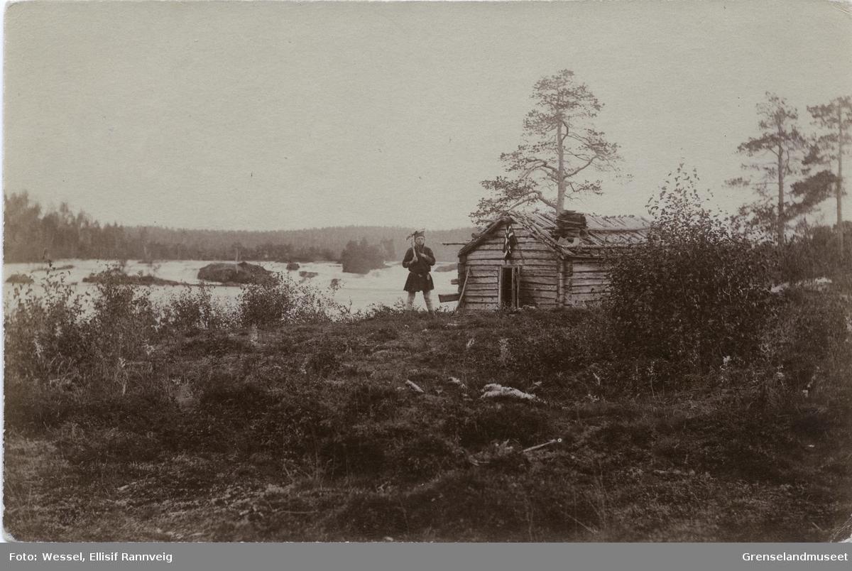 "Fra Skogfoss ""Männikafoss"", september 1896. Ole Johnsen Must står foran koia med en øks over skulderen."
