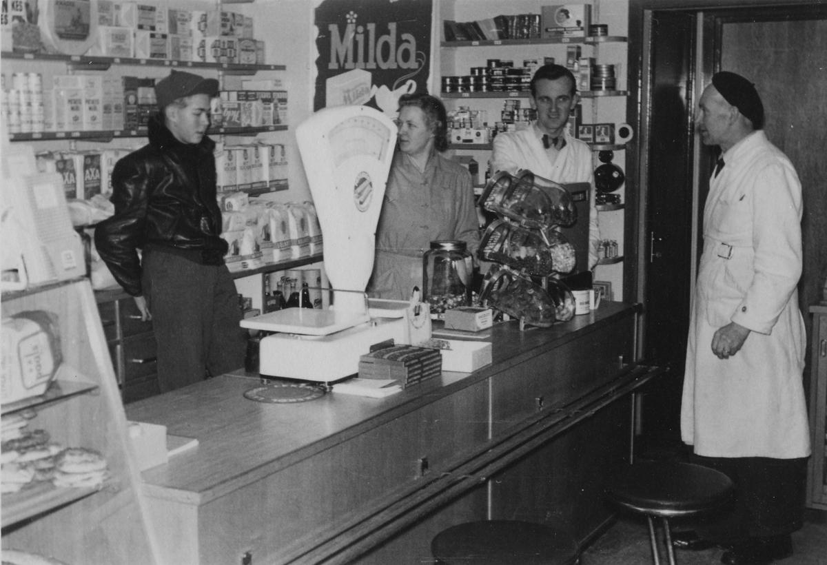 Från vänster: Ove Kjell-Svärd - Margit Kjell - Arnold Andersson - Edvin Kjell fotograferad i Kjells speceriaffär som låg i hörnet Hemvägen - Lärkvägen. På väggen bakom dom en reklamskylt för Milda.