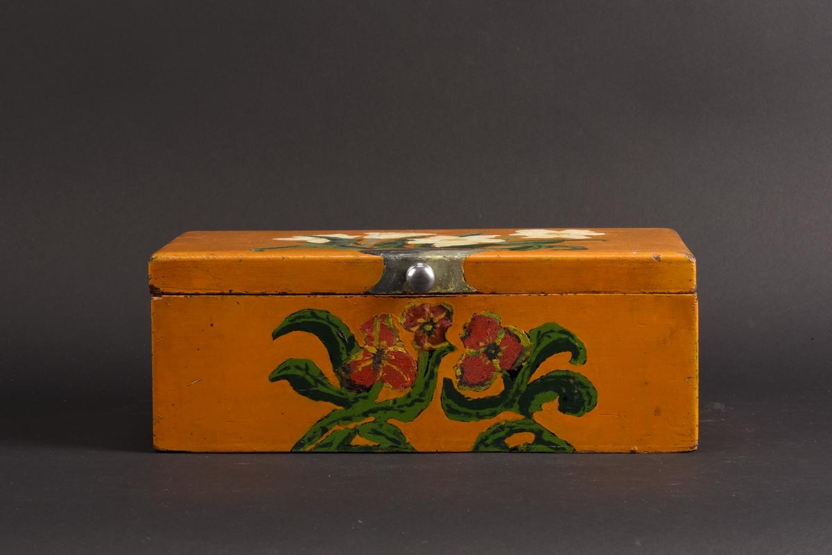 Rektangulärt syskrin med lock tillverkat av trä. Skrinet är gulmålad och dekorerat med vita och röda blommor samt gröna blad. Locket är fäst med gångjärn och har en knopp i metall. Inuti är skrinet klätt med mörkrött sammetsfoder och är indelat i fack, ett större och två mindre. Ovanpå de mindre facken finns en löst låda indelad i två fack.