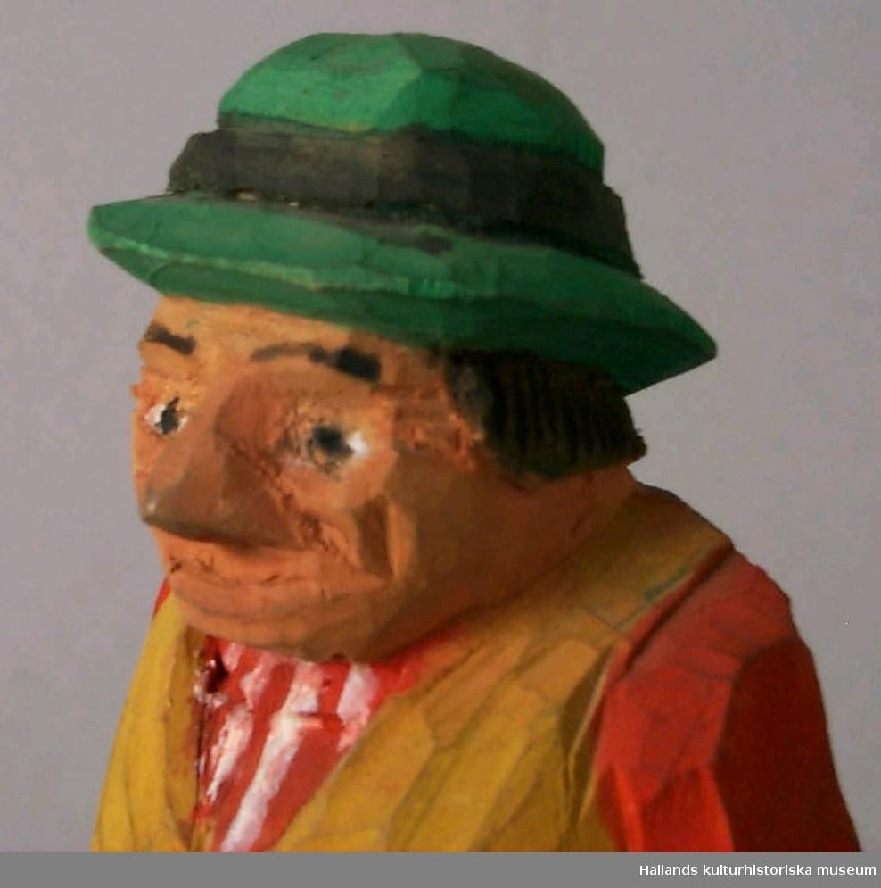"""Snidad mansfigur i trä. Kläder i grönt, rött och gult samt svart och gulbrunt. Står på mindre platta, händerna i byxfickorna.Märkning: """"Gustav Jonasson Hemmeslöv 1961""""."""