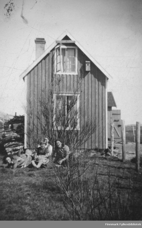 Pareli Cato W Eriksen sitt hus i Børselv. Tre kvinner og ei jente sitter utenfor huset. Fuglehus henger ved siden vinduet i 2. etasje.