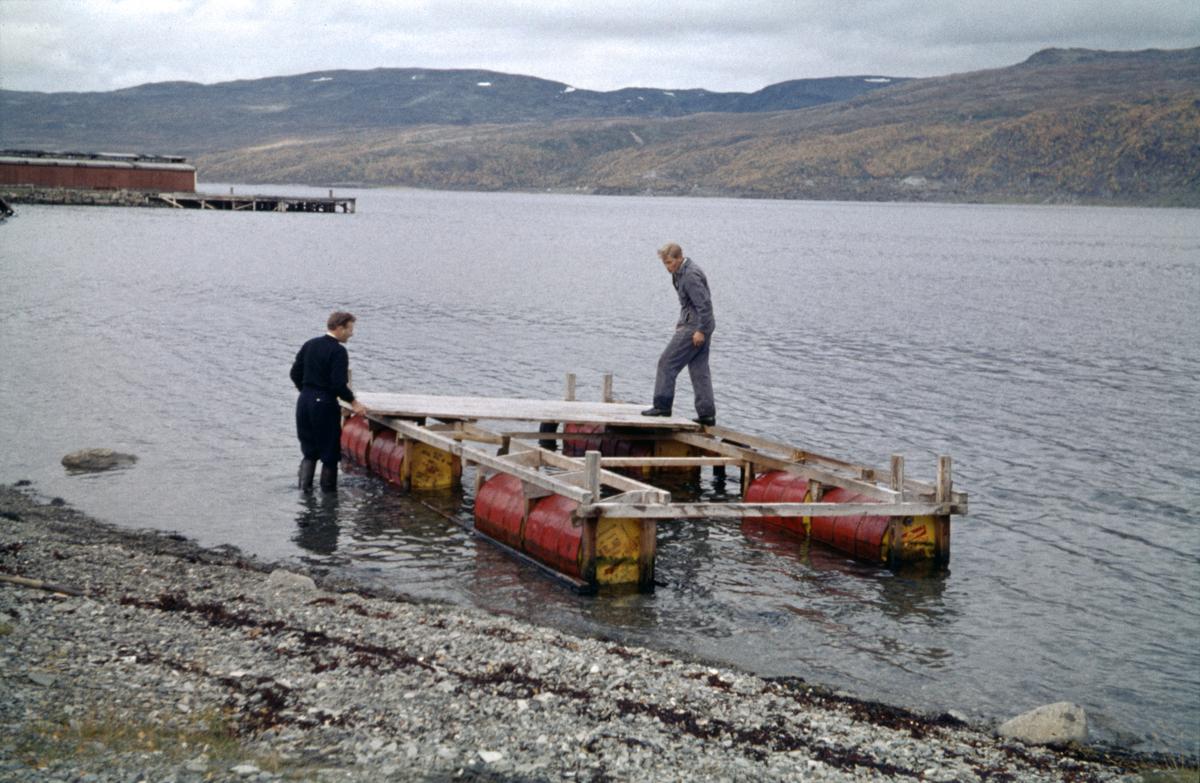 To mann i sving med å reparere eller bygge ei flytebrygge for sjøfly.
