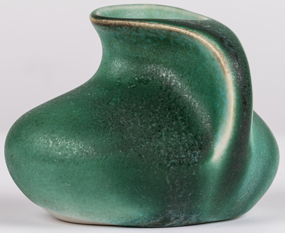 Liten rund vas med grön, matt glasyr. Oregelbunden form.