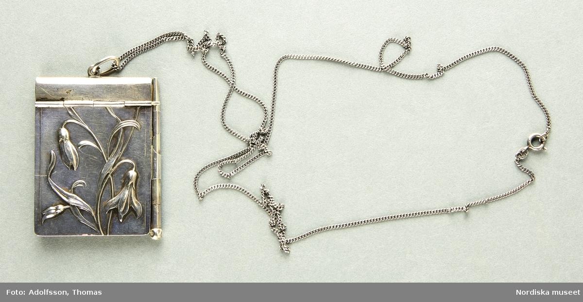 a-c) Ett dansprogram-halsband i jugendstil. a) Dansprogrammetspärm tillverkat i silver, framsidan med reliefdekor av böljande blomsterstjälkar. På dansprogrammets ena långsida är en ögla för fästandet av b) den medföljande lilla smala silverpennan. På dansprogrammets ena kortsida finns en öga där c) en lång silverhalskedja av tunnare pansarmodell är innträd, för praktiskt hängande dansprogrammet runt halsen. Dansprogrammet innehåller flera papperssidor, samtliga med guldkant. På vissa av sidorna står kvinnonamn, vissa endast förnamn andra med fullständigt namn. Sista datumanteckningen är 20/12 1975 och sista anteckningen är Hariette Astrid,  /Cecilia Wallquist 2019-02-21
