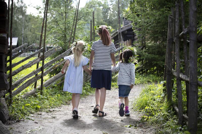 3 jenter med blomsterkranser går hånd i hånd