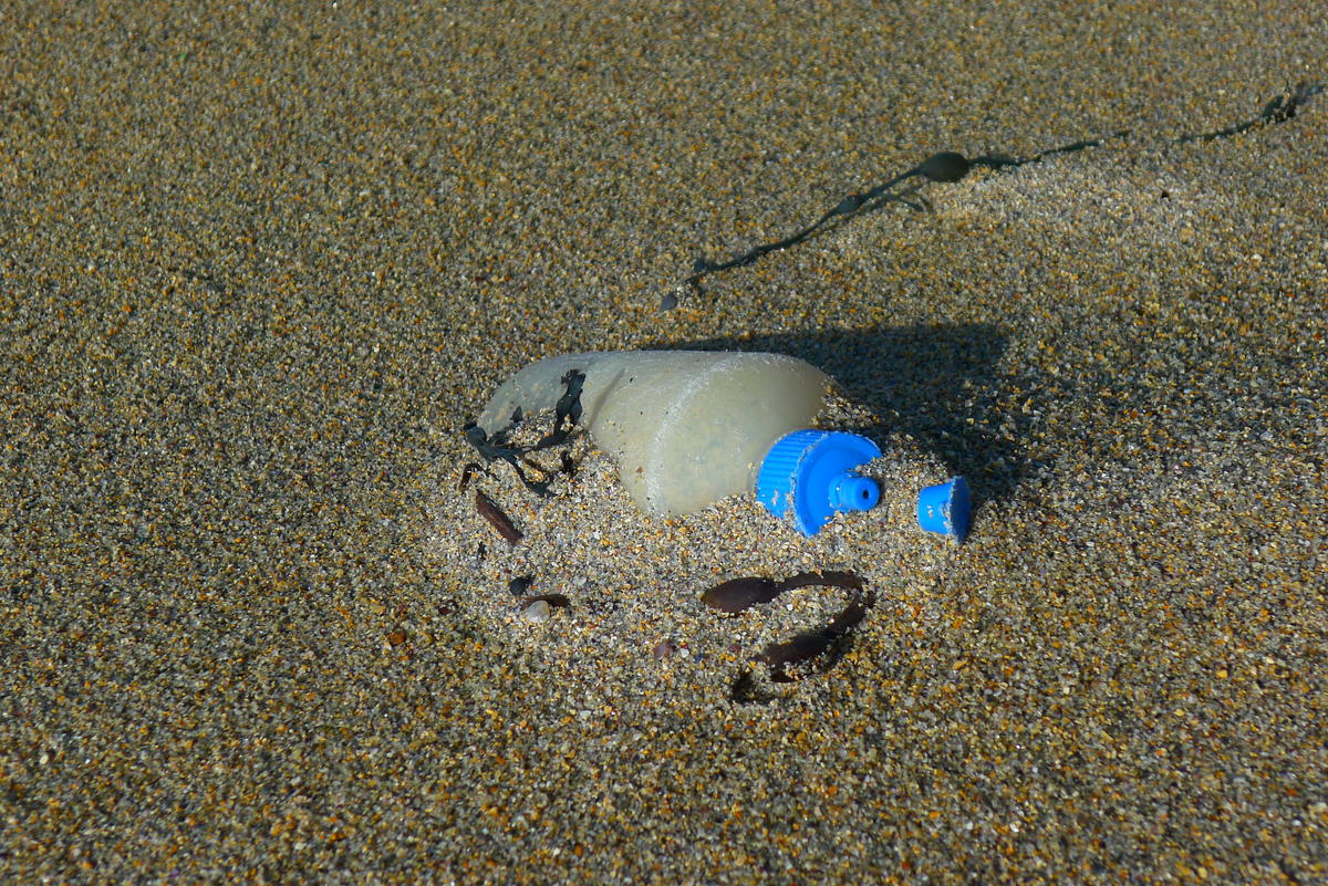 Brun sandstrand der det stikker opp en gammel spenolflaske av sanden.