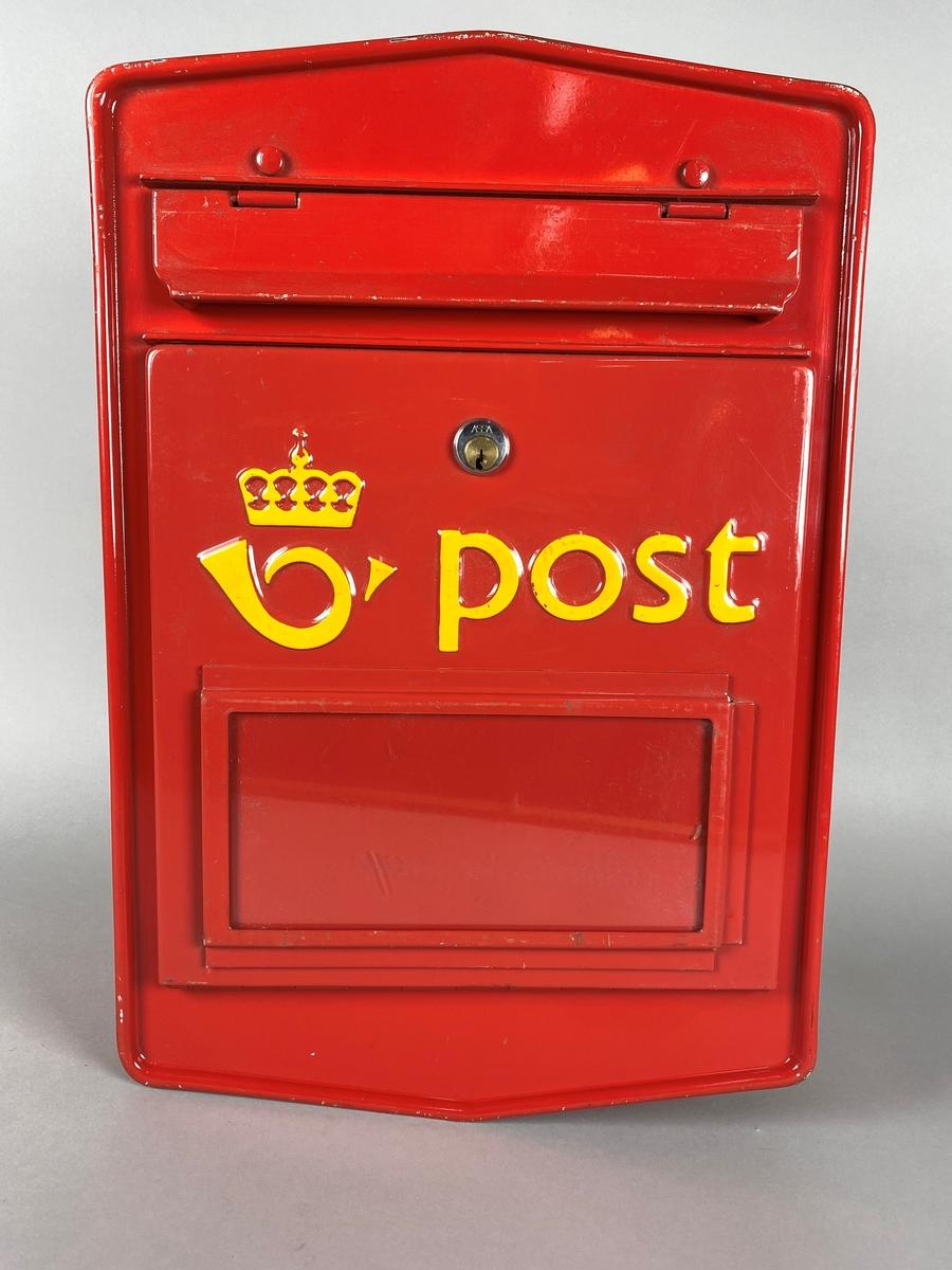 """Rød postkasse med """"vindu"""" for tømmeplakat. Med luke for innslipp av brev, og et låsbart lokk i front for tømming av post. Gul postlogo og skrift."""