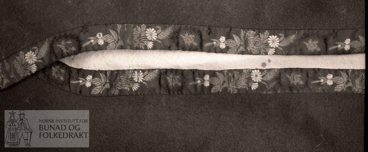 Mørkeblå vadmel i kypert. Fôra med ubleika bomullslerret. Kanta framme. Halsopning med svart silkeband med lansert blomemotiv i grønt, raudt og gult. Fire hekter i høgre og fire hemper i venstre side. Bakovertrekte skuldersaum og sidesaum. Innsett kile midt bak + nedrekant som endar i en svak vifteform midt bak. Glatt isydd erme med ein saum midt under erme - kanta nede med svart silkeband med lilla og grøne rosemotiv. Krok og hekte i ermesplitt. Sjå saumbeskrivelse og mønster.  Høgde rygg:               51,1 cm.  Høgde under erme:           25 cm.  Høgde kile:               10,5 cm.  Høgde framkant (rett ned):  40 cm.  Breidde band:              2,4 cm.  Breidde band halsopning:   1,5 cm.