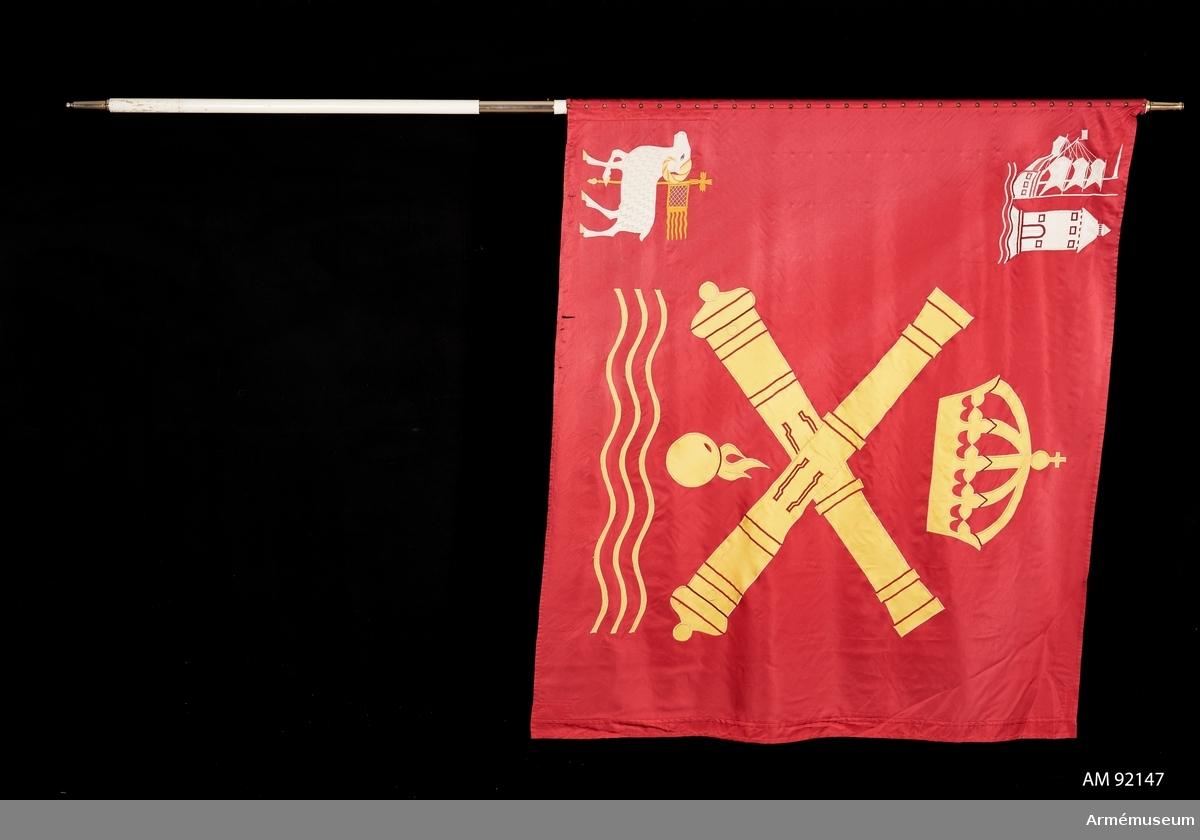 """Duk av rött siden. I mitten kustartilleriets vapenbild: två korslagda eldrör under kunglig krona och över en flammande granat och vågor. Allt i gult. I övre inre hörnet staden Vaxholms vapenbild och i nedre hörnet Gotlands vapenbild.  Vitmålad stång. Holk av förgylld mässing med gravyr """"Vaxholms amfibieregemente 2003"""". Holk av förgylld mässing. Skarvrör med bajonettfattning. Spets saknas."""
