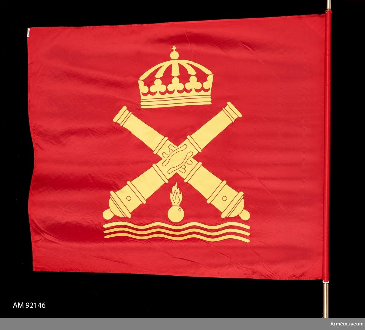 """Duk av rött siden. I mitten kustartilleriets vapenbild: två korslagda eldrör under en kunglig krona över en flammande granat och vågor. Allt i gult. Motivet utfört i applikation. Holk av förgylld mässing med gravyr """"Kustartillericentrum 1995"""". Doppsko i guldfärgad plast."""