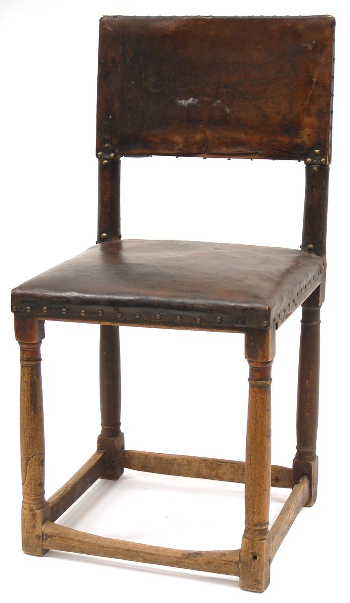 Stol, med raka svarvade ben, skinnklädd sits och ryggfyllnad, upptill. Smala slåar nertill mellan alla benen. Märkt OOS (+symbol, korslagda flaggor)