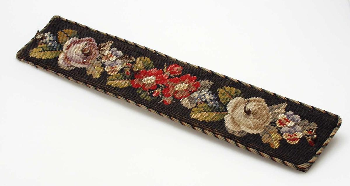 Fôret treplate med brun fløyel på baksiden og flerfarget tvunnet bånd langs kanten. Fronten er heldekket med korssting. Svart bunn, fylte roser i beige, brunt, grågult og småblomster i gult-rødt-blått i hver side. To røde enkle blomster og to-tre knopper, blad i midten. Motivet er brodert med ulltråd på stramei. 5 messingskruer satt i. Den 6. mangler. To messingringer på baksiden for oppheng.