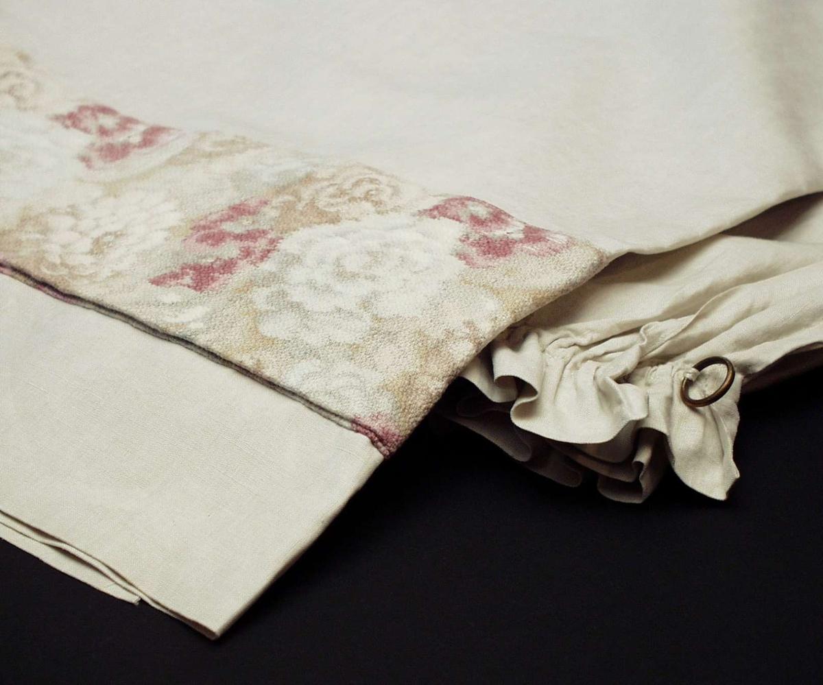 Portiere i lin med påsydd remse av trykt blomstret stoff. Fargen er gråhvit med dekor i lilla, hvitt og grått.