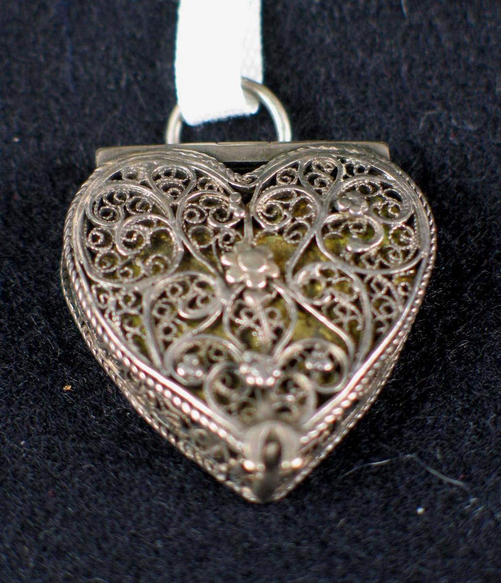 Sølvanheng i filigran formet som et hjerte. Forgylt plate som synes gjennom det gjennombrutte mønsteret.