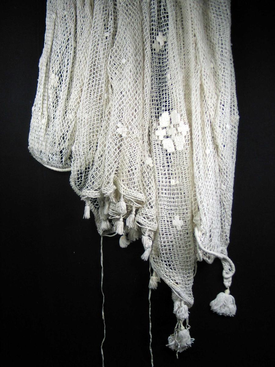 Sledenett i løst tvunnet bomull, knyttet som et fiskegarn. Maskevidde ca 1,5 cm. Det er delt inn i tre felt. Midtfelter er ca 110 cm og knytt til to 3 cm brede heklete border med dusker i sidene. Stivt kledd reip i hver kortside, hvor nettet er festet. Dusker og påsydde bendelbånd. Prikker og kryss sydd inn i nettet med filèrteknikk. Spredt utover.