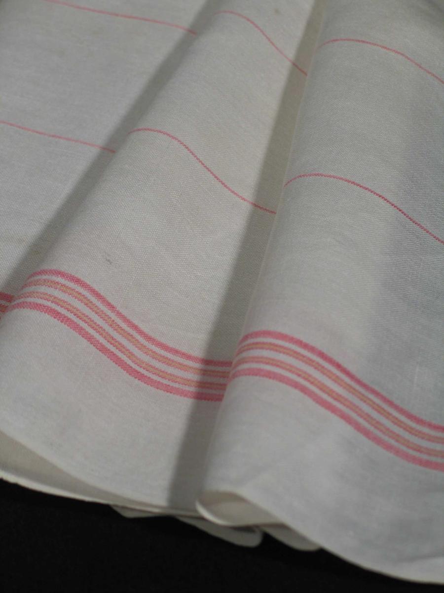 Hvitt glasshåndkle i lin med røde og gule striper i bord øverst og nederst. Fem smale røde striper fordelt over flaten. Stripene ligger i renningen, og er antatt av bomull. Vevbredden 66 cm med jare, maskinsydde falder øverst og nederst.