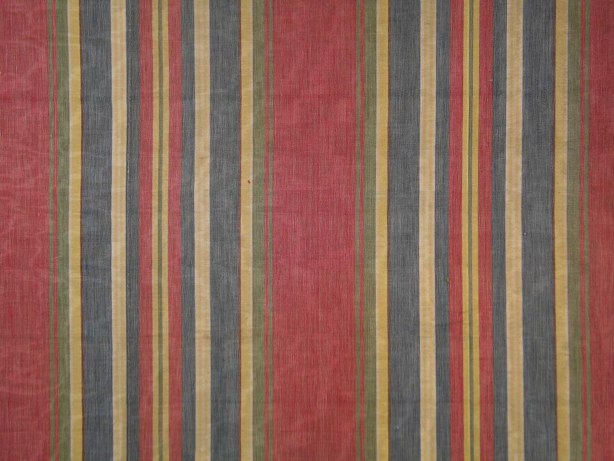 Rest av stripete bomullsstoff i fargene rødt, gult, grått, hvitt, gulgrønt og brunt. Striper i ulike bredder, rapport 32,4. Vevbredden er 131 cm. Mercerisert renning.  Merker etter opplegg/spretting.