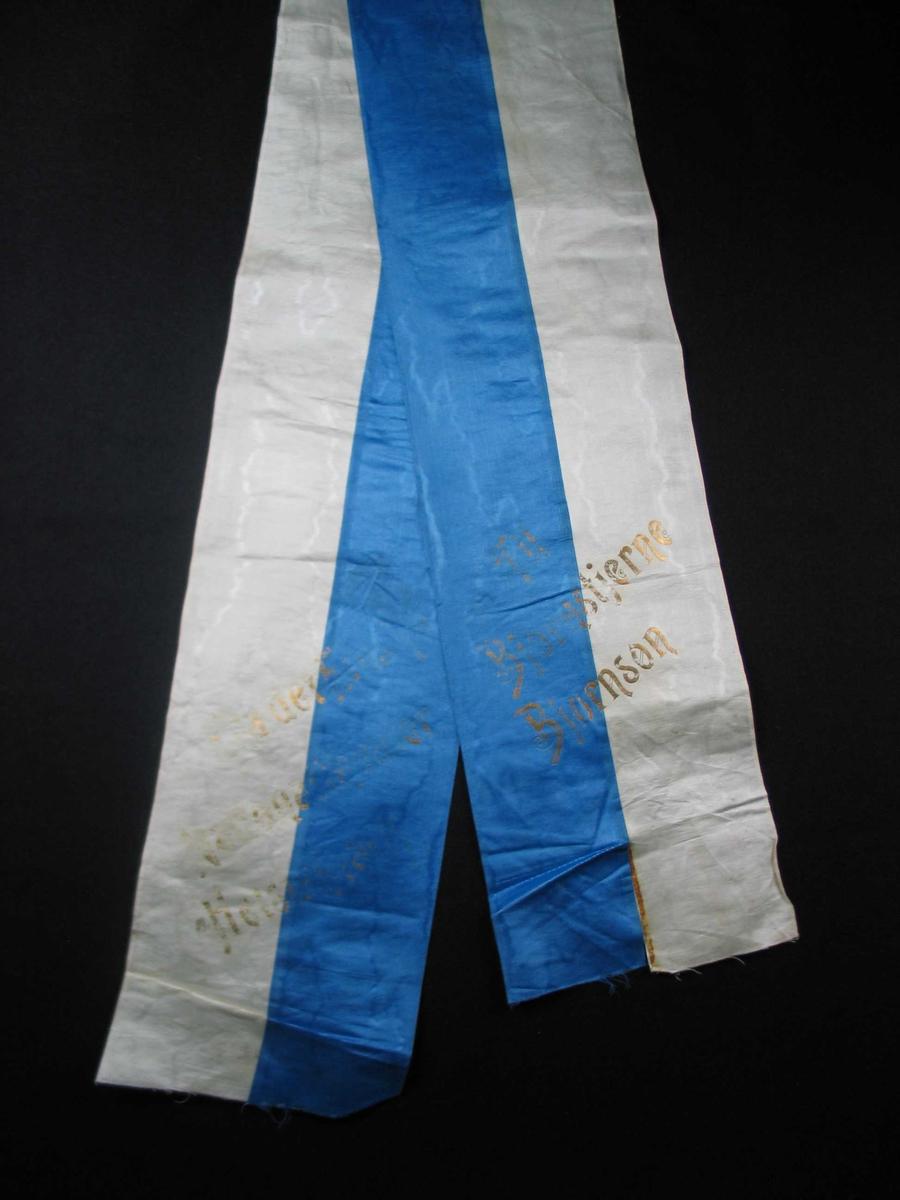 Begravelsessløyfe i hvit og blå silke med tekst i gull.
