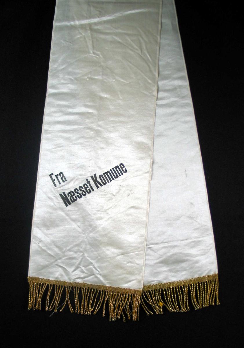 Begravelsessløyfe i hvit silke med svart tekst og gullfrynser.