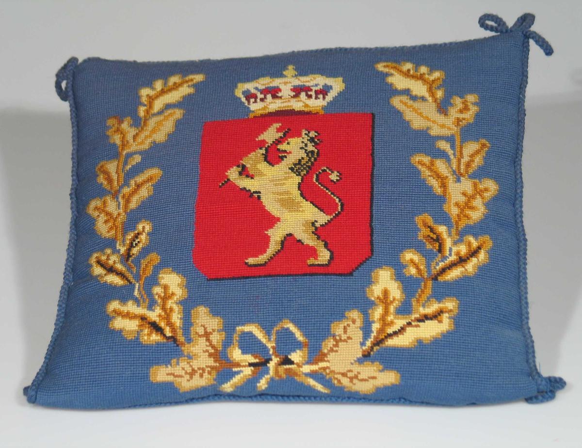 Pute brodert i petit point. Forestiller den norske løve. Bunnfarge i blått med broderi i rødt, gult og brunt. Tvunnet blå snor som danner sløyfer i hjørnene. Bakstykke i blå silkerips.