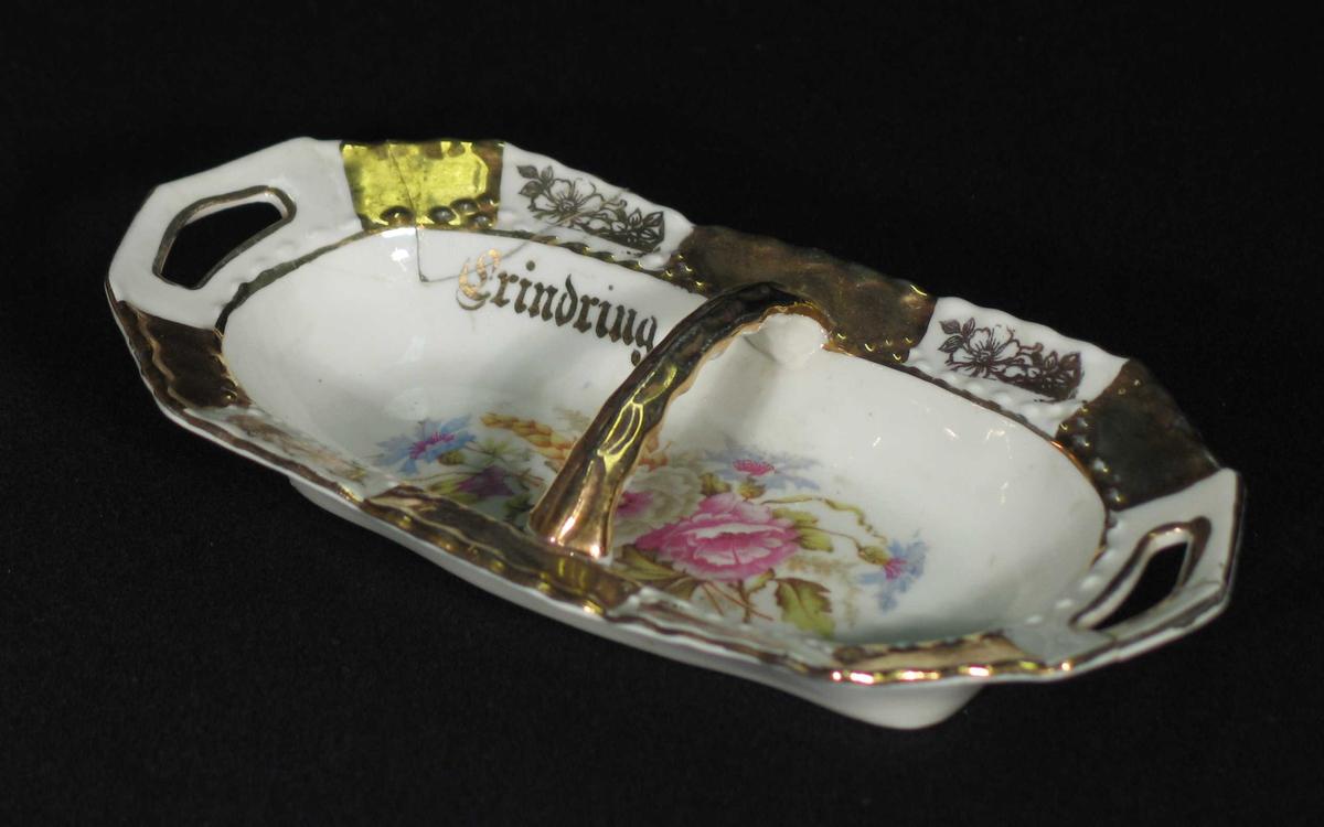 Rektangulær skål i porselen med brutte kanter. Den har to håndtak og hank tversover. Bunnfargen er hvit med forgylte felt og et trykt blomstermotiv i bunnen.