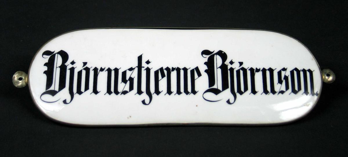 Ovalt hvitt dørskilt i porselen med navnet malt i svart. Metallomramming og feste for oppheng i hver side.