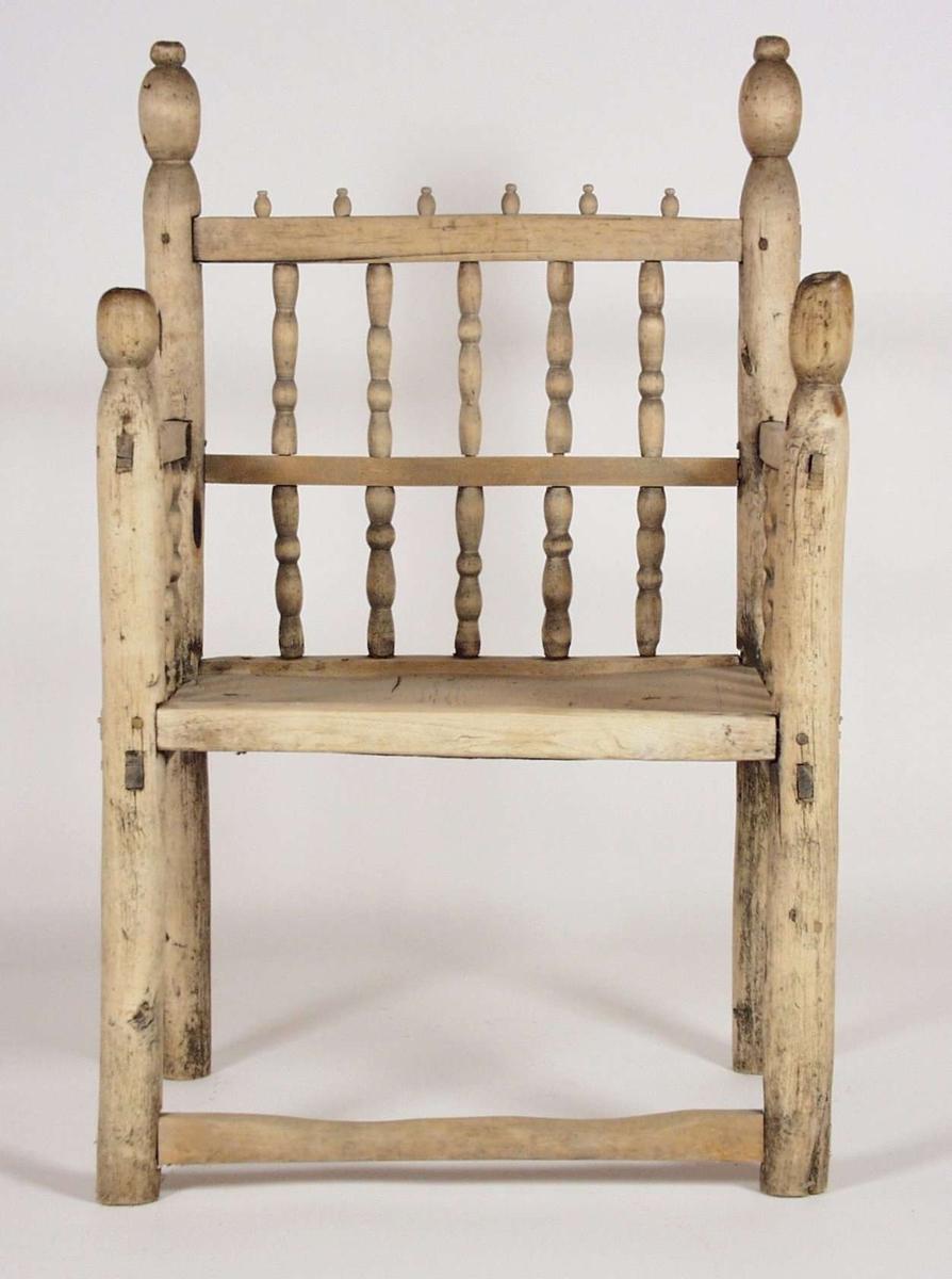 Stolpestolen er av bjørk og har dreide spiler i rygg og sider. Bakbena, som fortsetter helt opp til stolryggen, og forbena avsluttes i dreide kuler.
