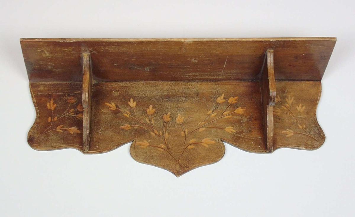 Hyllen er i bjørk. Rektangulær hylleplate båret oppe av to kontursagde konsoller festet til en kontursaget rygg. Ryggen er dekorert med enkle blomsterutskjæringer.