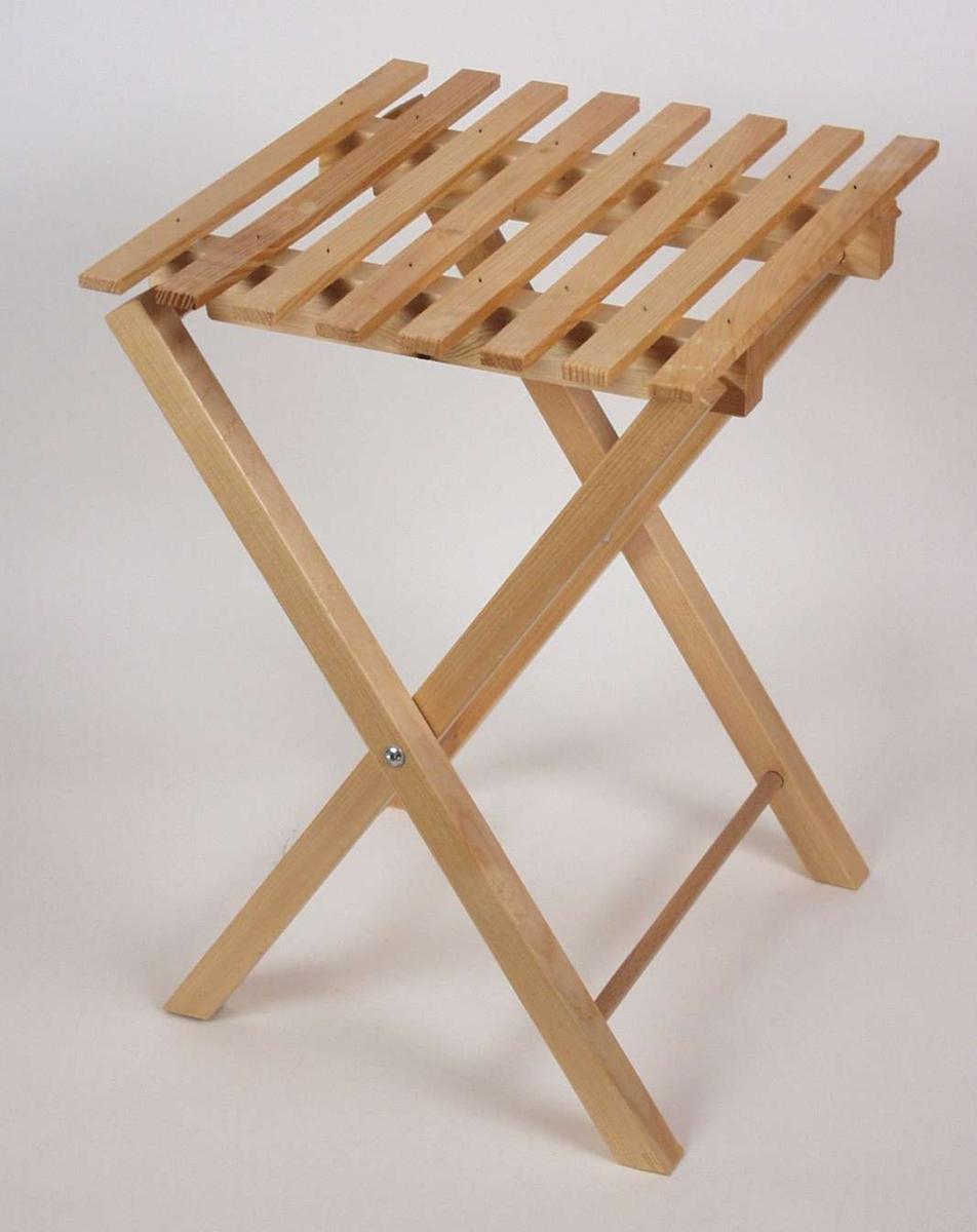 Enkelt sammenleggbart blomsterbord i lakkert furu. Understellet er en bukk som er festet til bordplaten på den ene siden. Bordplaten er firkanta og er satt sammen av spiler.