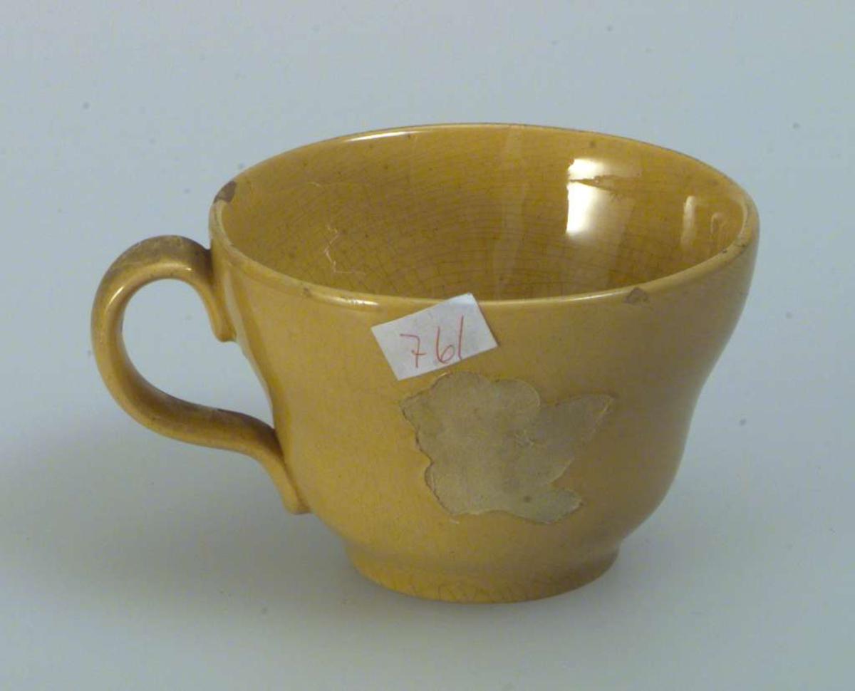 Gul kaffe-/tekopp med skål. Dekoren på koppen er falt av. Skålen er uten dekor. Det er hakk i både koppen og skålen. Det er ingen produksjonsmerker på kopp eller skål.