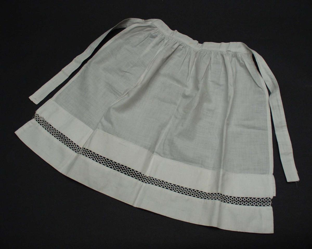 Bunadskjorte til pike, med mellomverk i nupereller. En synål med tråd i viser at noen har arbeidet med å feste  nuperellene.