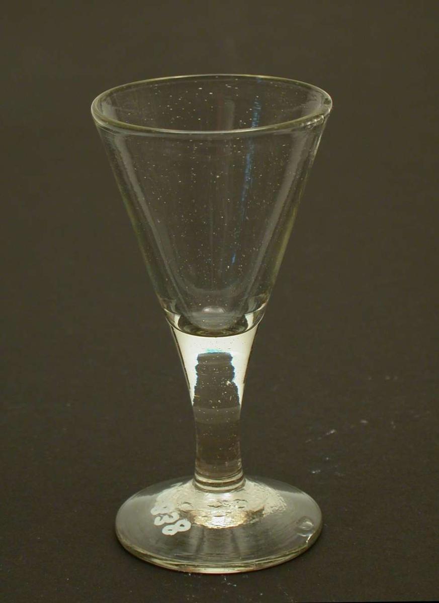 Spissglass. Glasset har et svakt grønnskjær. Glasset er sprukket og har et hakk i randen.