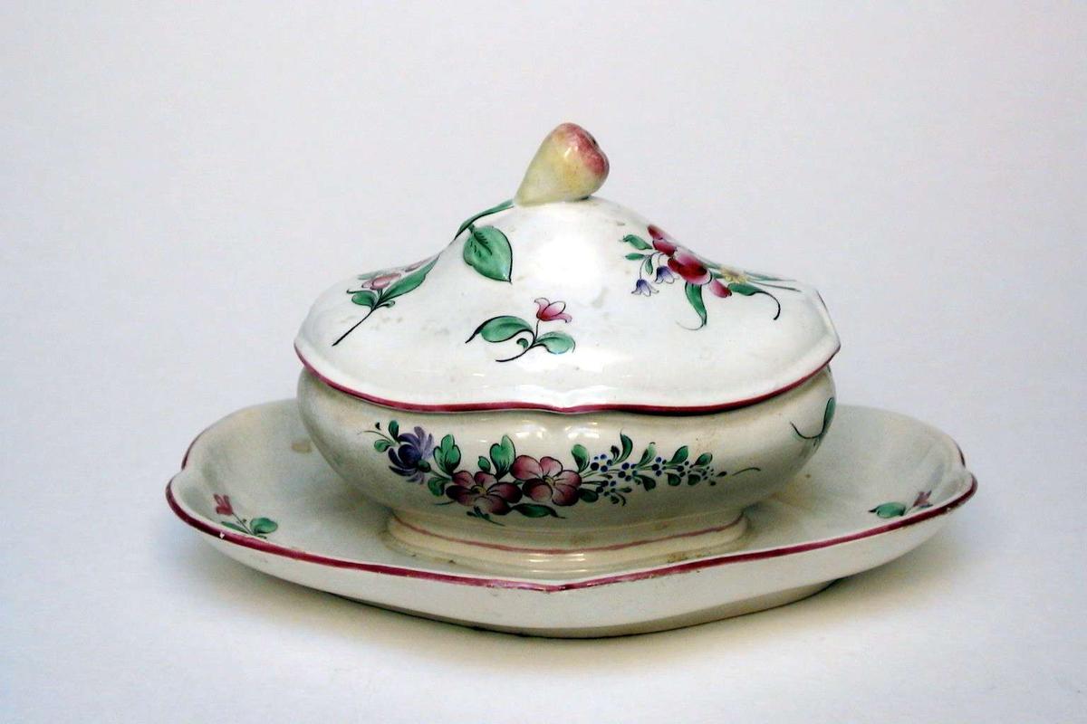 Sauskopp med lokk i kremfarget keramikk med polykrom blomsterdekor. Den har bokstaven C og et tegn (en lorgnett) preget i godset. Lokket har en pære som lokkgrep. Lokket ser nytt ut i forhold til koppen som er noe misfarget.