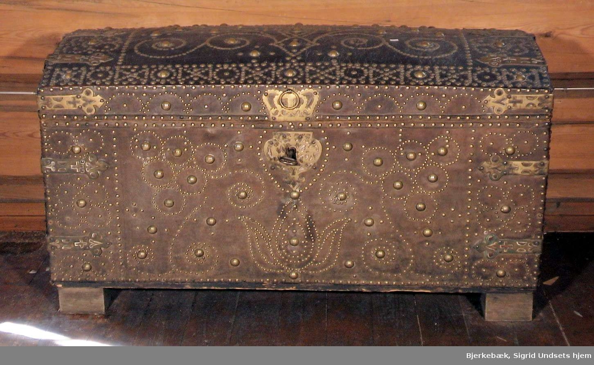 Lærtrukket kiste med dekorasjoner og beslag av messing på yttersiden. Kisten har håndtak, lås og nøkkel av jern. Det er to rom innvendig. Kisten står på fire føtter, hvorav en av føttene er ødelagt. Innsiden av kisten er trukket med mønstret papir.