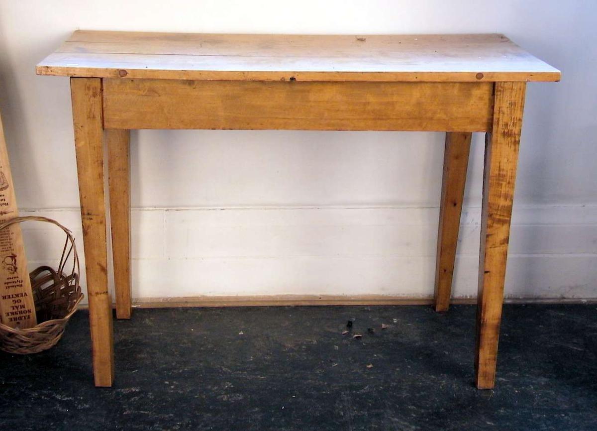Rektangulært bord med rette ben. Bordet er lyslakkert.