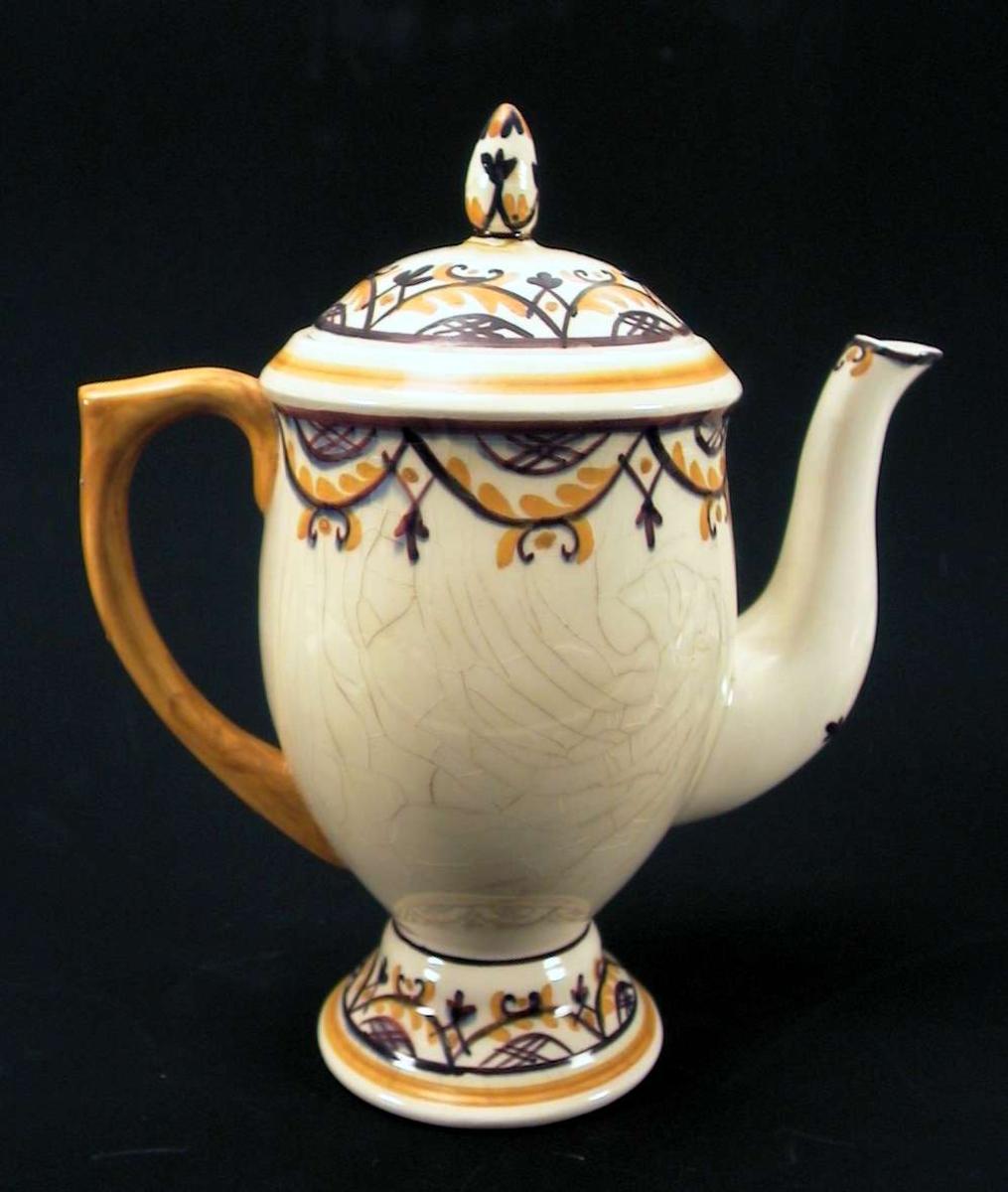 Kaffekanne med lokk i lys gul fajanse med håndmalt dekor i lilla og oker. Glasuren er krakelert på kannens korpus. Lokkgrepet er limt på.