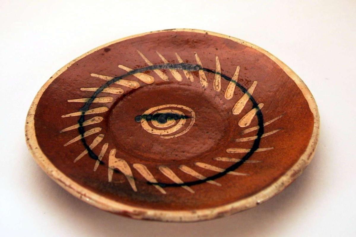Grovt laget skål i brunt leirgods med 'meksikansk' dekor.