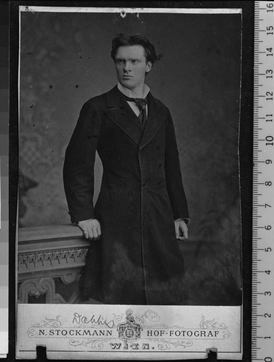 Portrettfotografi av ung mann i lang mørk jakke med hvit skjorte med opprettstående flip og løstbundet slips.