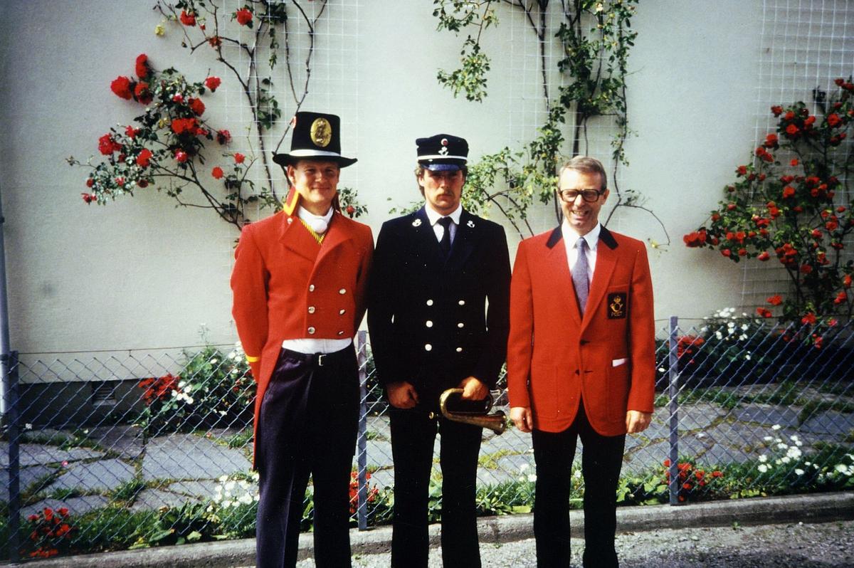 uniformer, to menn i gammel dansk postuniform og en mann i gammel norsk postuniform utenfor Rosendal Baroni, posthorn, roser