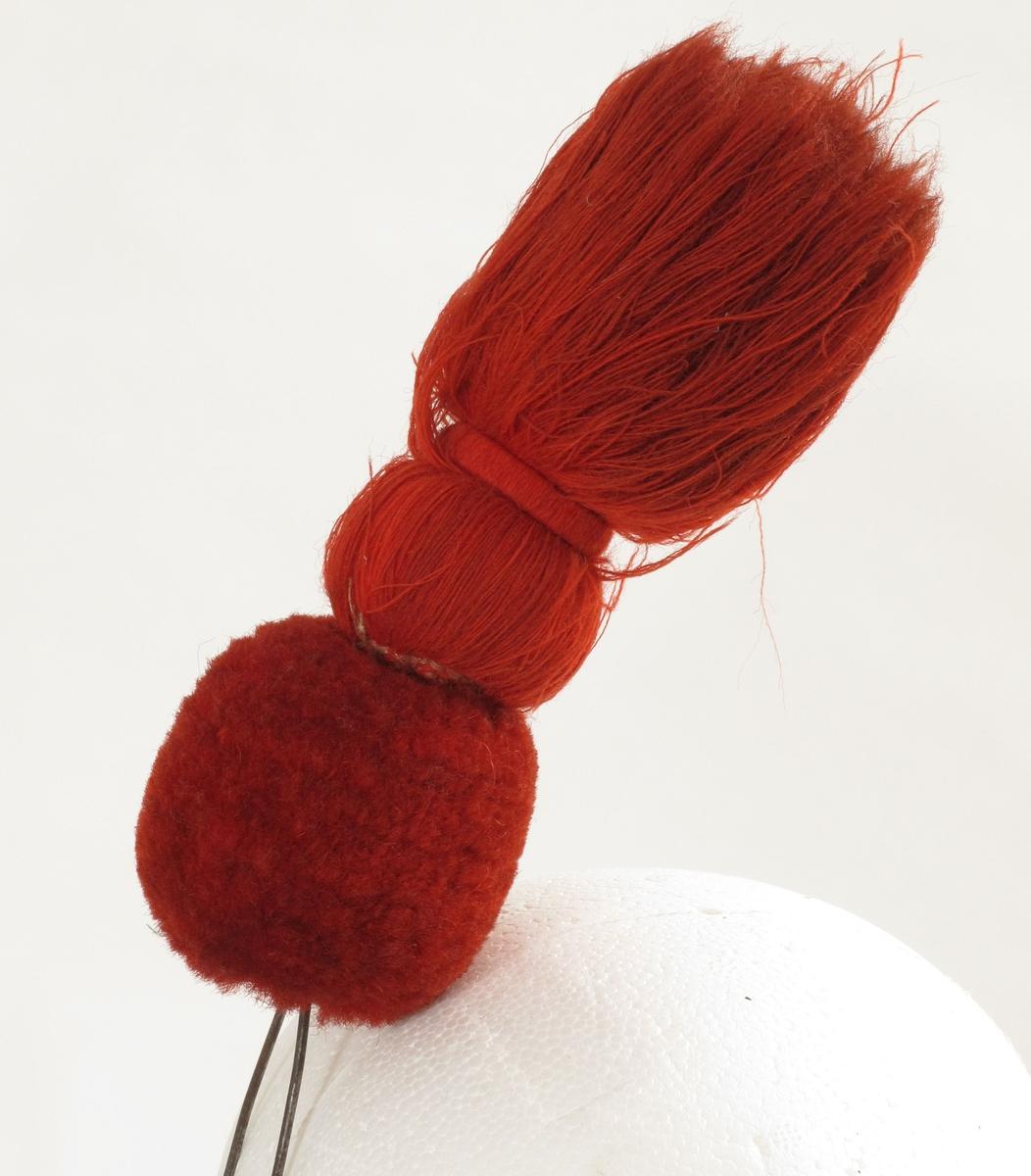 Ponpon av ull, rød, fasong: brennende bombe, med den nedre kule av langhåret plysj.  Ståltrådbøyle til å feste på uniformsluen. Tilhørende uniform AAM.00198.