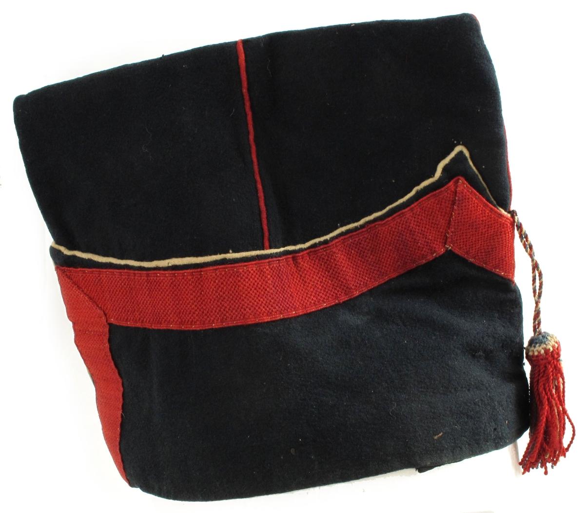 """Uniformslue. Sort klede, høy båtluefasong med bred """"oppbrett"""" kantet med bredt rødt bånd og hvit passepoil.  I forkant festet en dusk i snor i fargene rødt, hvitt og blått.  Røde passepoils på pullen.  For:  Sort lakkskinn. Tilhørende uniform AAM.00198"""