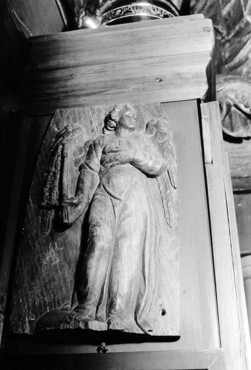 Engel; kropp frontal, h. arm på brystet, i v. hånd svøpe ?, hode høyrevendt