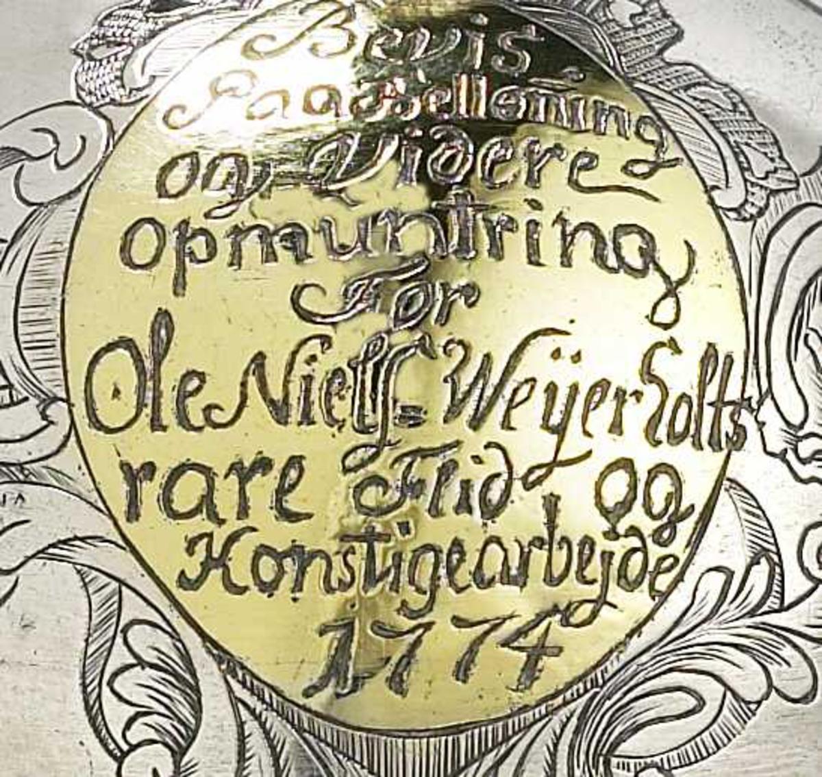 Smal munningskant.  inngravert  i full høyde tre tulipaner,  på kort stilk og med korte rundflikede blad, dels oppstreket med korte streker, oppbygd. Lokk kronet av en kongleformet toppknott. På den ene side en oval med våpenskjold  med en rose omgitt av tre vinger, hjelmbekroning en hånd som holder bue: våpenskjold ført av Niels Scythe, foged i Nedenes 1770 -83. På den annen side tilsvarende oval, omkranset av rokokko skjellformer øverst og C-former på siden.