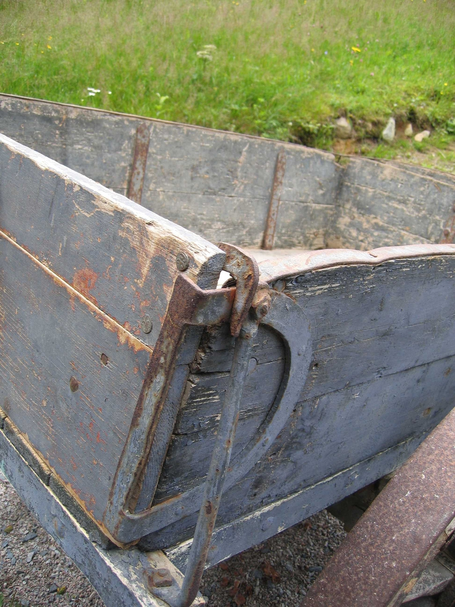 Tung gjødselkjerre med mange beslag. Hjul av tre med jernskoning. Låsen til tippmekanismen betjenes med et håndtak. Kantene på kassa beslått med jern. Fremkant og sider er sinket sammen. Hullene i dragene er beslått med jern på begge sider.