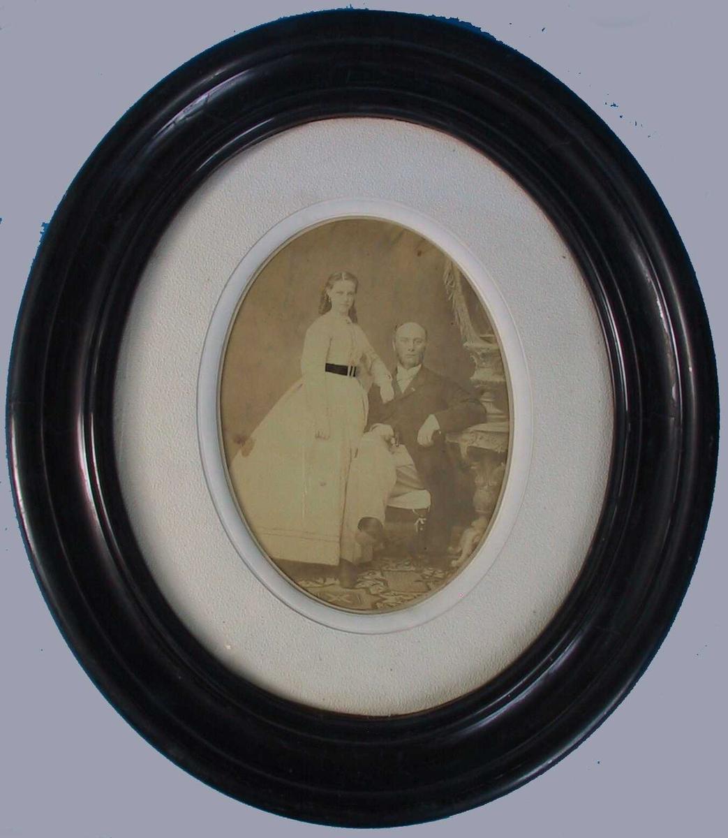 Portrett av Agathe og Johan Haemmerle,  Brudebilde 1866 (?).  Portrett av en  ung stående kvinne tv. , høyrevendt, i hvit kjole mdd sort belte. Kjolen er forknappet med en brosje i halsen, lange ermer, vidt skjørt med to den ene arm mot mannens skulder.  Mannen sitter med det ene ben over det annet, mørk frakk og vest, lyse benklær.  Stol med varetrekk, lener h. arm til utskåret konsoll i bord i nyrokokko med en urne på. Mønstret teppe