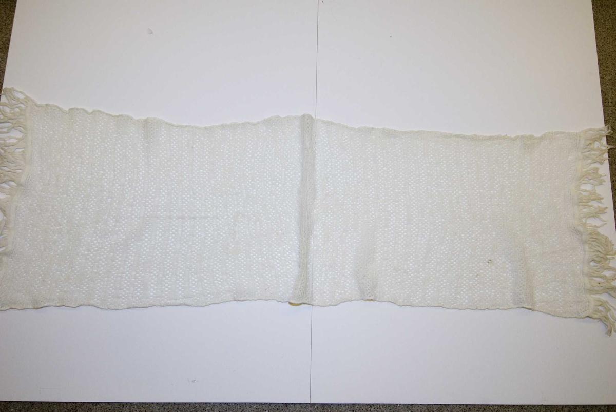 Hvitt mønstret sjal med påsydde frynser. Hullmønster.