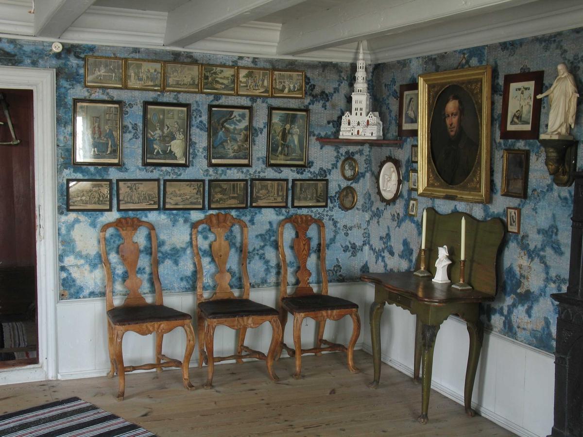 Merdøgaard. Interiør storstua. Bilder på veggen, stoler, velurtapet, brystpanel.